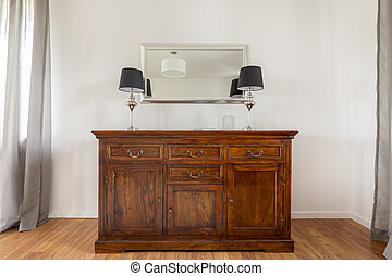 Closer shot of stylish wooden commode with two lamps on it...