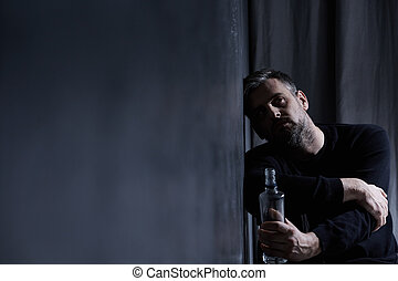 Man with alcohol bottle - Depressed man sitting alone with...