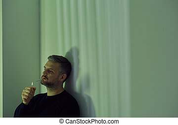 Man lighting a cigarette - Depressed man sitting alone and...