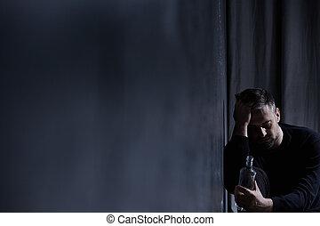 Man staring at alcohol bottle - Broken mature man staring at...