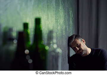 Man with empty alcohol bottles - Man suffering from...