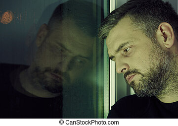 Man near the window - Depressed man looking sadly through...