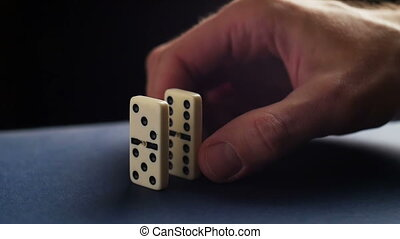 Closeup of a hand putting a domino. Dominoes falling. Nervous and failure.