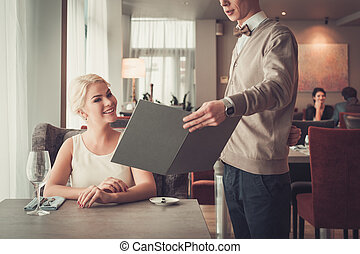 Waiter explaining menu to elegant woman in restaurant