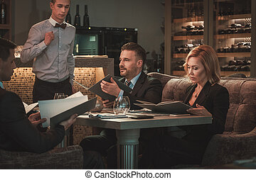 Group of successful business people with menu in restaurant