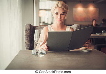Elegant blonde woman with menu in a restaurant.