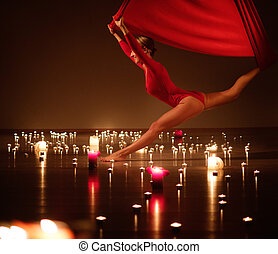 Young girl in red performing aerial yoga in relaxing candle...