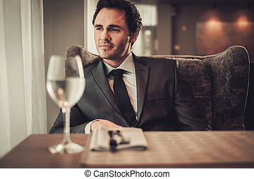 Confident young man sitting in restaurant waiting for...