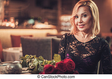 Portrait of beautiful middle aged woman with bouquet of red roses in restaurant