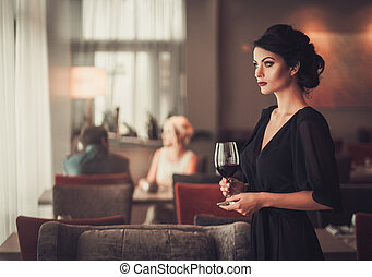Elegant brunette lady in black evening dress with glass of red w