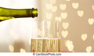 Glasses with champagne, wedding rings and hearted bokeh on wedding day