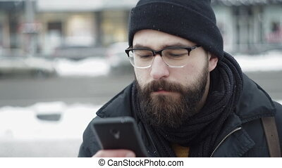 Beard Man typing sms on phone outdoors