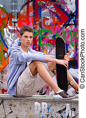 Cool-looking young man in front of graffiti