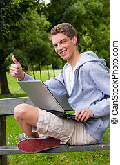 Young man with laptop computer outdoors
