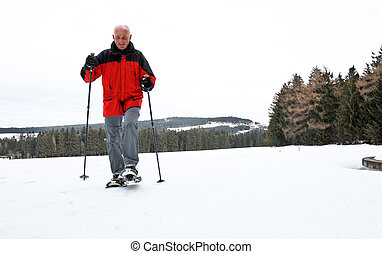 Senior at the snow-shoe walking in winter