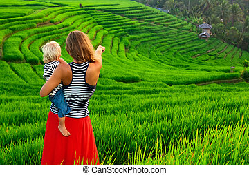 Mother with child walk on green rice terrace. Bali -...