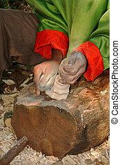 african hands making a wooden candlestick holder
