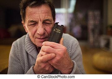 Senior man praying, holding Bible in his hands, eyes closed....