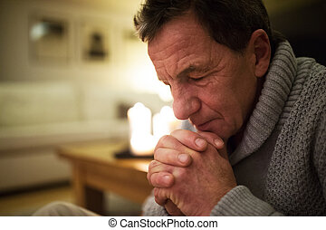 Senior man at home praying, burning candles behind him. -...