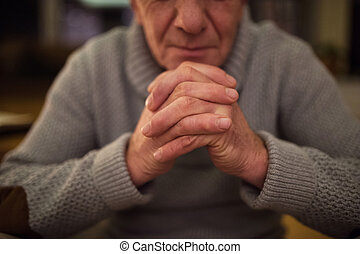 Unrecognizable senior man at home praying, hands clasped...