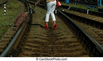 Girl cross the rails. Girl with a suitcase.