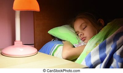 Man's hand turned out the light from a table lamp in crib fallen asleep girl