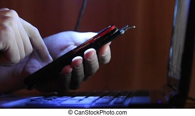 Hands typing on your smartphone working at a laptop,...