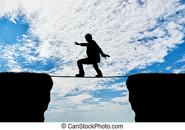 Man walks on a tightrope over a cliff. Concept of business...