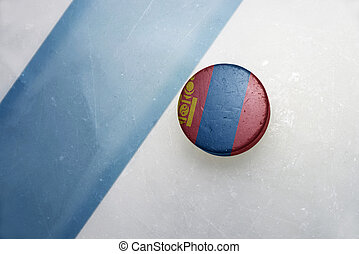 old hockey puck with the national flag of mongolia. -...