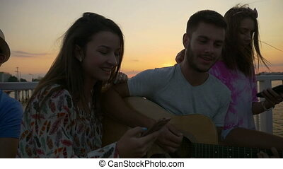 Friends singing on summer time with a guitar on a bridge in slow motion