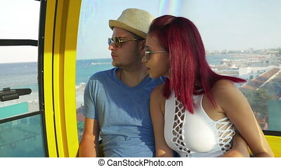Young couple on the ropeway at the seaside watching the...