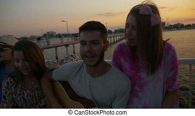 Boys and girls sitting on a bench and singing on a pontoon