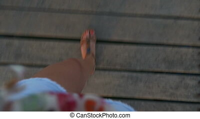 Pov feet of a woman walking on a pontoon