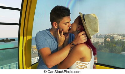 Lovers kissing passionately in ropeway at the seaside