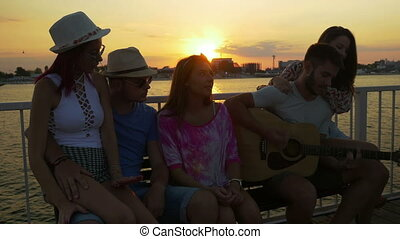 Group of friends sitting on a bench and singing with a...