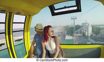 Lovers in a ropeway sightseeing the seaside