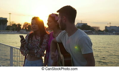 Three friends singing with a guitar on a bridge over the sea...