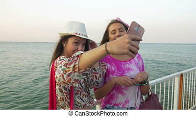 Girls taking selfie on a pontoon with the sea as a...