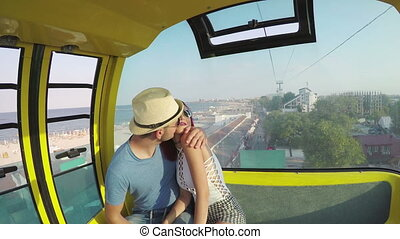 Couple in ropeway enjoying the view and kissing