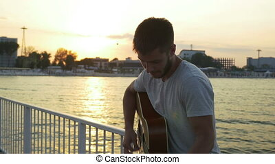 Young man singing at the guitar on a bridge over the sea
