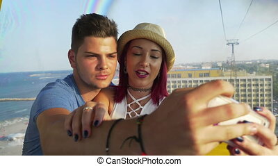 Lovers kissing and taking selfie in the ropeway