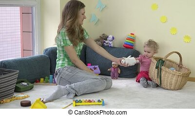 mother woman with adorable toddler daughter girl put toys in...