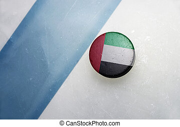 old hockey puck with the national flag of united arab...