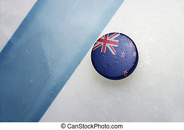 old hockey puck with the national flag of new zealand. -...