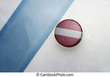 old hockey puck with the national flag of latvia. - vintage...