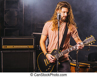 Young man playing electric guitar on stage
