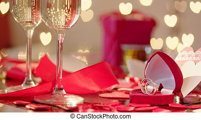 Wedding rings and glasses filled with champagne, hearted...