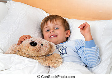 Child lies in bed in the bedroom - A small child lies in bed...