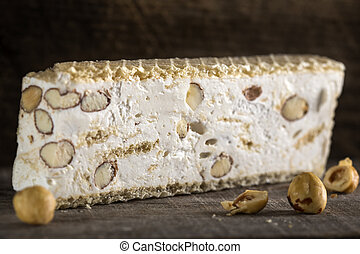 Close up of torrone or nougat with nuts on wood background