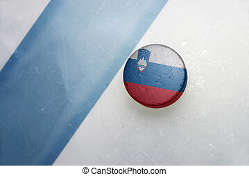 old hockey puck with the national flag of slovenia. -...
